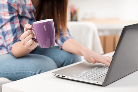 Woman with coffee and laptop